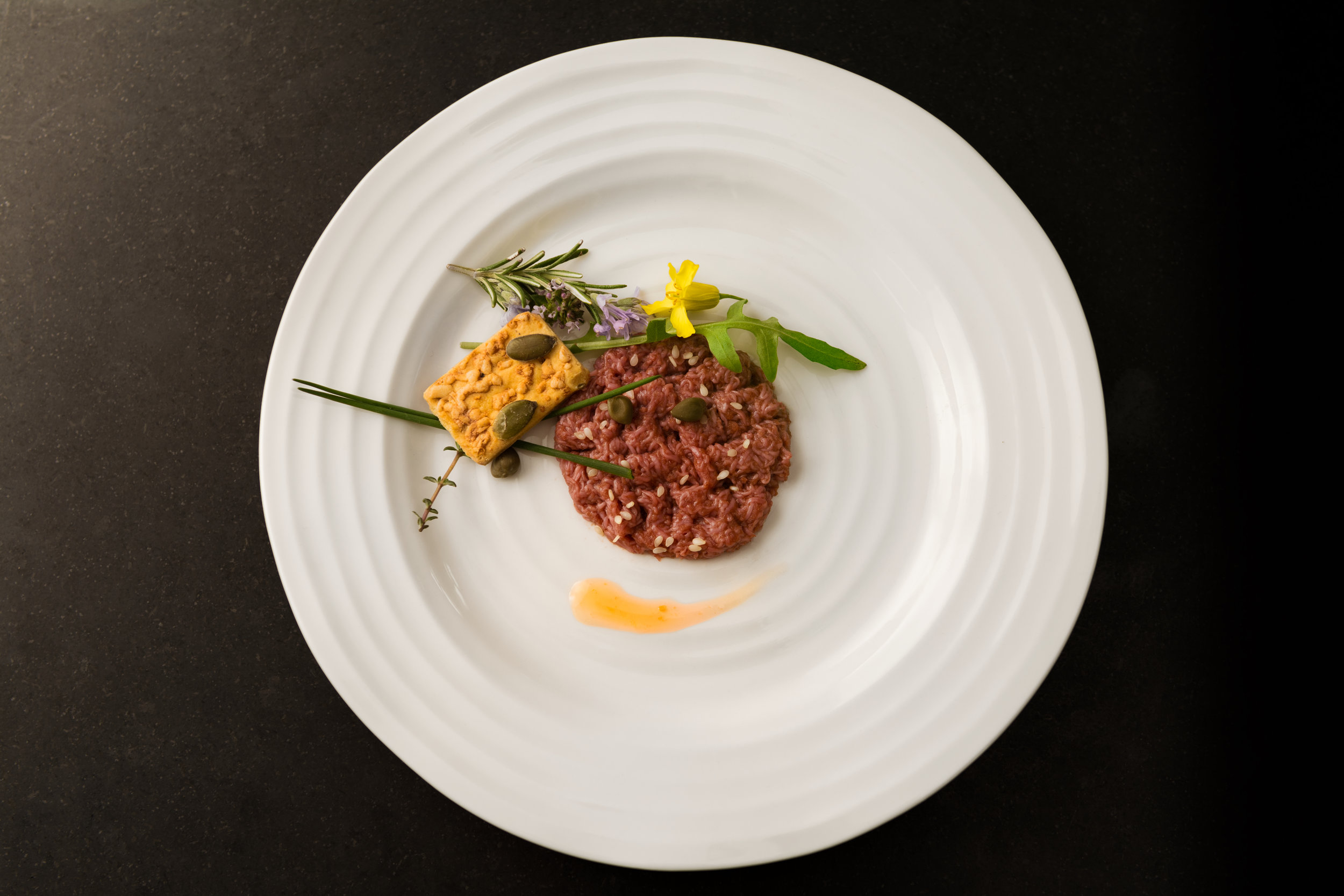 Mosa Meat's steak tartare on white plate with garnishes